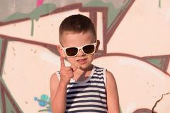 Boy wearing sunglasses and shirt on graffiti background lifted index finger up royalty free stock photography