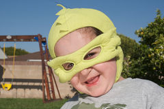 Boy wearing super hero costume. Smiling boy wearing green super hero mask, looking to camera. In the back, playground Royalty Free Stock Photography