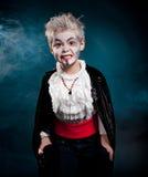 BOy wearing vampire for halloween. Boy wearing as vampire for halloween. Blue fog on the background Royalty Free Stock Photo