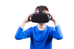 Boy wearing virtual reality glasses watching movies or playing video games, isolated on white background. Royalty Free Stock Image