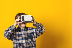 The boy wearing virtual reality goggles over yellow background. Stock Images