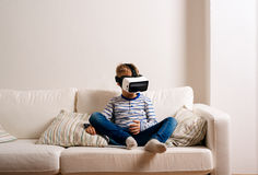 Boy wearing virtual reality goggles. Studio shot, white couch Stock Photos