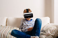 Boy wearing virtual reality goggles. Studio shot, white couch Royalty Free Stock Photography