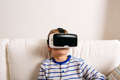 Boy wearing virtual reality goggles. Studio shot, white couch Royalty Free Stock Photos