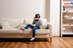 Boy wearing virtual reality goggles. Studio shot, white couch Royalty Free Stock Images