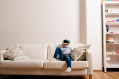 Boy wearing virtual reality goggles. Studio shot, white couch. Little boy in striped t-shirt wearing virtual reality goggles, sitting on white couch in a living Stock Images