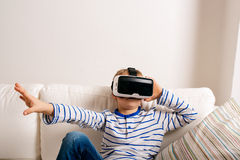 Boy wearing virtual reality goggles. Studio shot, white couch Stock Image