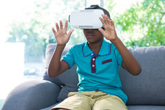 Boy wearing virtual reality headset with arms raised at home Stock Images