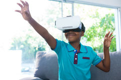 Boy wearing virtual reality headset gesturing at home Stock Images