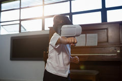 Boy wearing virtual reality simulator gesturing while standing at home Stock Images