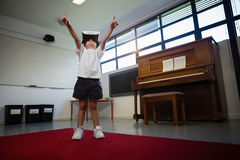 Boy wearing virtual reality simulator raising hands while standing against piano Royalty Free Stock Images