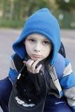 Boy wearing warm coat. Portrait of boy wearing warm blue coat with hood outdoors Royalty Free Stock Image