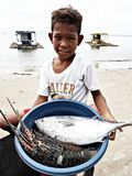 Boy Wearing White Crew-neck T-shirt Holding Blue Plastic Basin Full of Lobster and Fish stock photo
