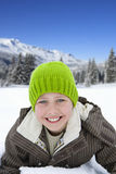 Boy (7-9) wearing woolen hat, lying on snow, smiling, portrait, close-up Stock Photo