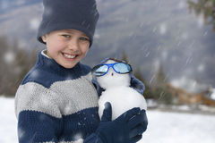 Boy (7-9) wearing woolen hat in snow field, holding mini snowman, smiling, portrait Royalty Free Stock Image