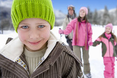 Boy (7-9) wearing woolen hat in snow, smiling, portrait, close-up, family in background Royalty Free Stock Photography