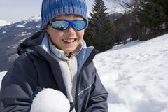 Boy (7-9) wearing woolen hat and sunglasses in snow field, holding snow ball, smiling, portrait Stock Images
