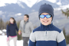 Boy (7-9) wearing woolen hat and sunglasses in snow, smiling, portrait, parents in background Stock Photo