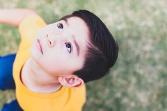 Boy Wearing Yellow Crew-neck T-shirt and Blue Bottoms Outfit Looking Above royalty free stock image