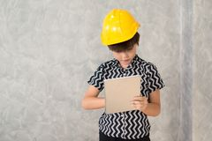 A boy wearing a yellow safety helmet are working with a digital Stock Photos