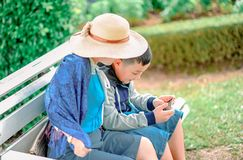 Boy Wears Gray, Blue, and Black Zip-up Jacket Holds Smartphone Next to Person Wears Beige Sun Hat Both Sits on Gray Wooden Bench stock images