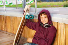 Boy wears hood and holds skateboard while sitting Stock Photos