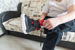 The boy wears running shoes sitting on a sofa in Stock Photos