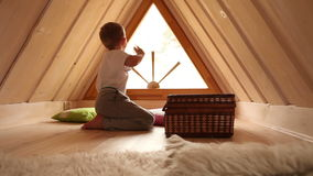 Boy welcomes somebody and waving hand from his attic room stock footage