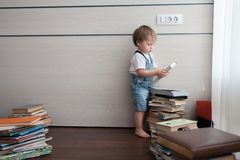 The boy went to a pile of books. royalty free stock images