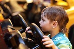 Boy at the wheel of car simulator Royalty Free Stock Photo