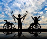 Boy in wheelchair and disabled boy standing with crutches day. Boy in wheelchair and disabled boy standing with crutches near sea and reflection. Concept Stock Images