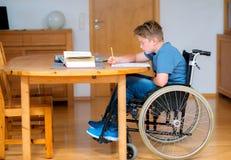 Boy in wheelchair doing homework Stock Photo