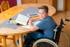 Boy in wheelchair doing homework Royalty Free Stock Images
