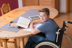 Boy in wheelchair doing homework Stock Images