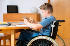 Boy in wheelchair doing homework and using tablet pc Stock Photography