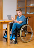 Boy in wheelchair doing homework and using tablet pc Royalty Free Stock Image