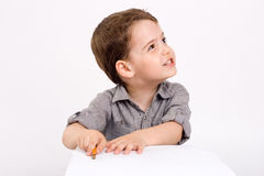 Boy which drawing of pencil. The little boy which drawing of pencil in notebook Stock Image