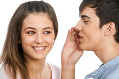 Boy whispering in cute girls ear. Close up of boy whispering to cute girl.Isolated on white Stock Photography