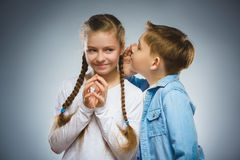 Boy whispering in ear of teen girl on gray background. Communication concept. Teenage boy whispering in the ear of teen girl on a gray background. Positive human Royalty Free Stock Photo