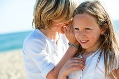 Boy whispering secrets to girl outdoors. Young boy whispering secrets to girl on beach Stock Photo