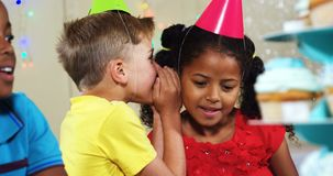 Boy whispering to girl while sitting with friends during birthday party 4k. Boy whispering to girl while sitting with friends during birthday party at home 4k stock video