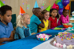 Boy whispering to girl while sitting with friends at table. During birthday party Stock Photography