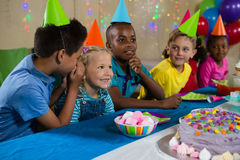 Boy whispering to girl while sitting with friends. At table during party Stock Images