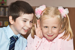 Boy whispers in her girlfriend's ear Royalty Free Stock Photography