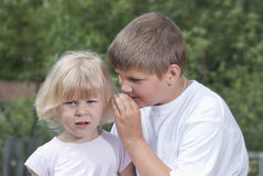 The boy whispers a secret to the girl. Children. The boy whispers a secret on an ear to the girl stock image