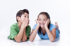 Boy whispers to sister. Royalty Free Stock Photography