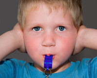 Boy with whistle. Young toddler blond boy blowing blue whistle while holding his ears shut Royalty Free Stock Photos