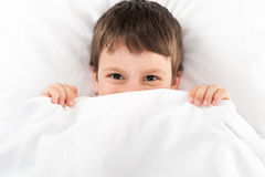 Boy in white bed Royalty Free Stock Image