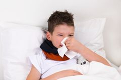 Boy in a white bed wipes his nose from a cold. Little boy in a white bed wipes his nose from a cold Royalty Free Stock Photos
