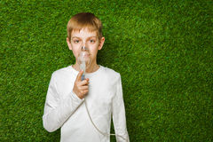 Boy in white breathing through inhalator mask Royalty Free Stock Photos